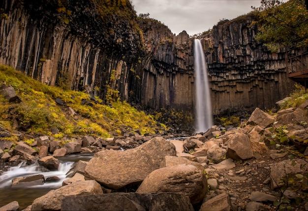 Cachoeira svartifoss cercada por rochas e vegetação sob um céu nublado em skaftafell, na islândia
