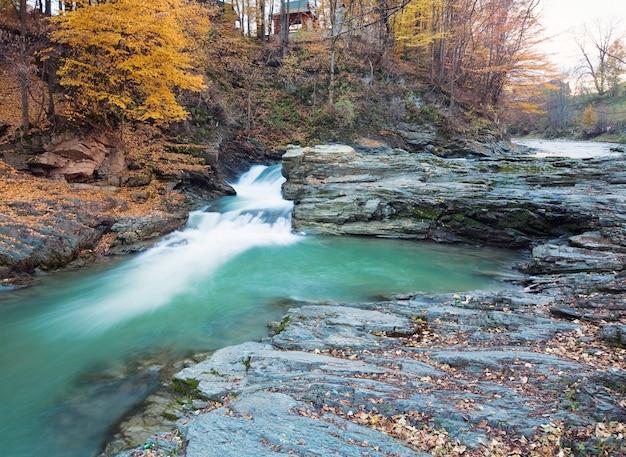 Cachoeiras no riacho rochoso, passando pela floresta de montanha de outono