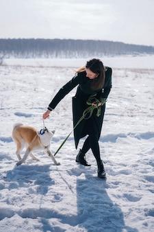 Cachorro akita inu com coleira verde brinca com brinquedo de corda com mulher de casaco verde escuro
