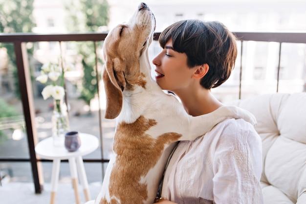 Cachorro beagle ergueu a cabeça e posou com as patas nos ombros da dona
