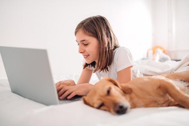 Cachorro dormindo na cama pela garota trabalhando no laptop