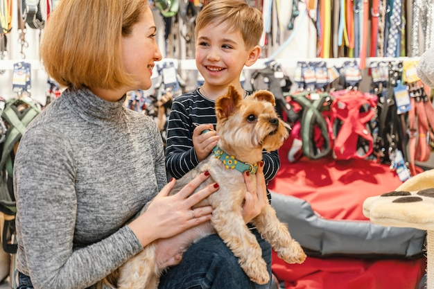 Cachorro fofo com donos na pet shop