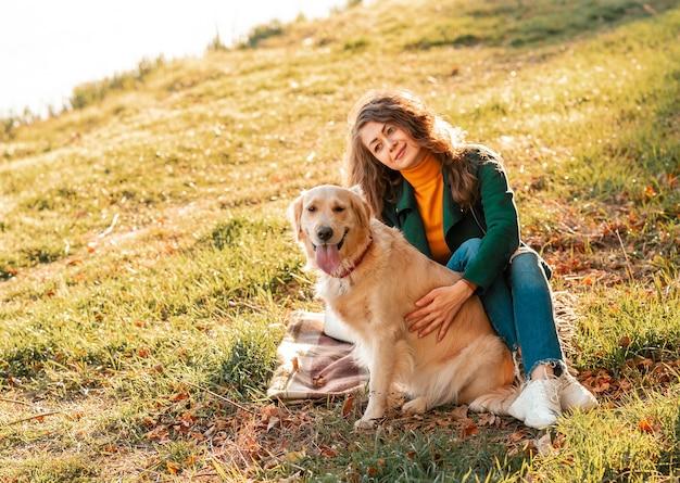 Cachorro golden retriever com uma mulher encaracolada ao ar livre em dia de sol