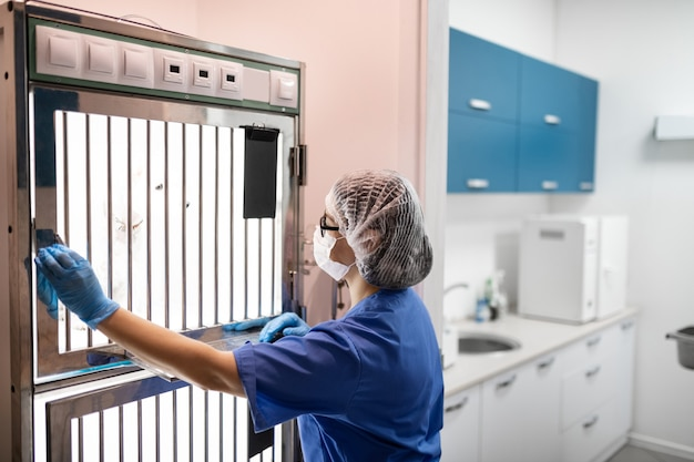 Cachorro na caixa. veterinário usando máscara retirando o cachorro da caixa especial para procedimentos médicos