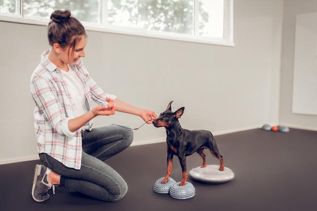 Cachorro preto. mulher de cabelos escuros vestindo jeans e camisa quadrada cuidando de seu cachorro preto