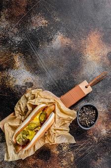 Cachorro-quente americano com linguiça de porco em uma tábua de madeira em kraft