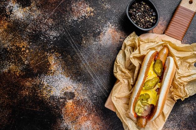 Cachorro-quente americano com linguiça de porco em uma tábua de madeira em papel kraft