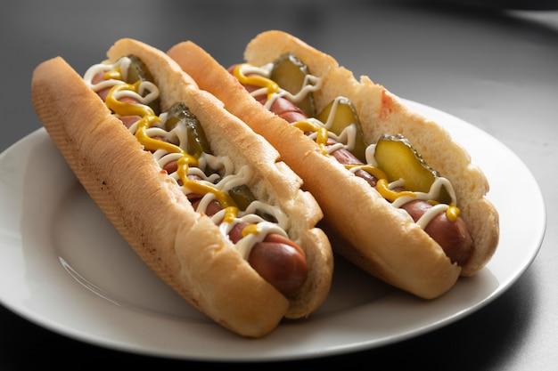 Cachorro-quente caseiro com salsichas e pepinos em conserva no prato