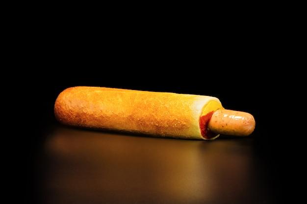 Cachorro quente checo - salsicha em um bolo do trigo com molho.