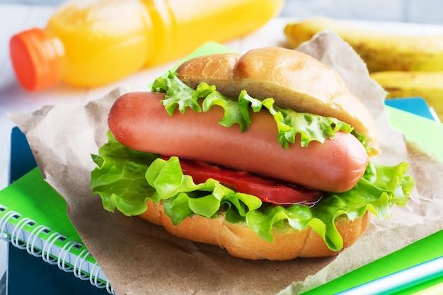 Cachorro-quente com alface tomate e salsicha. cadernos e artigos de papelaria. escola conceito café da manhã. copie o espaço.