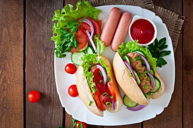 Cachorro-quente com ketchup, mostarda, alface e legumes na mesa de madeira