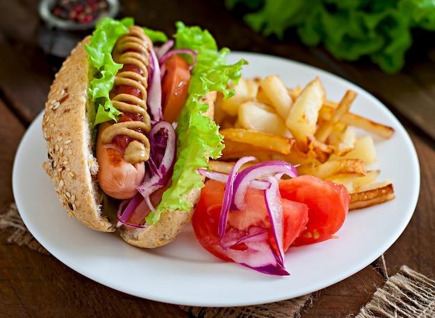 Cachorro-quente com ketchup mostarda e alface na mesa de madeira.
