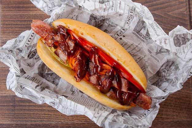 Cachorro-quente com linguiça, bacon, tomate e molho de tomate picante