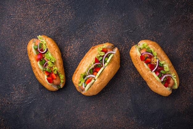 Cachorro-quente com linguiça, molhos e legumes