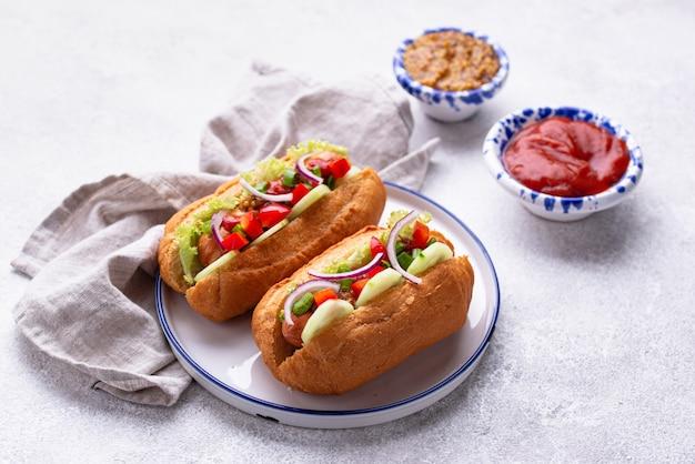 Cachorro-quente com linguiça, molhos e vegetais