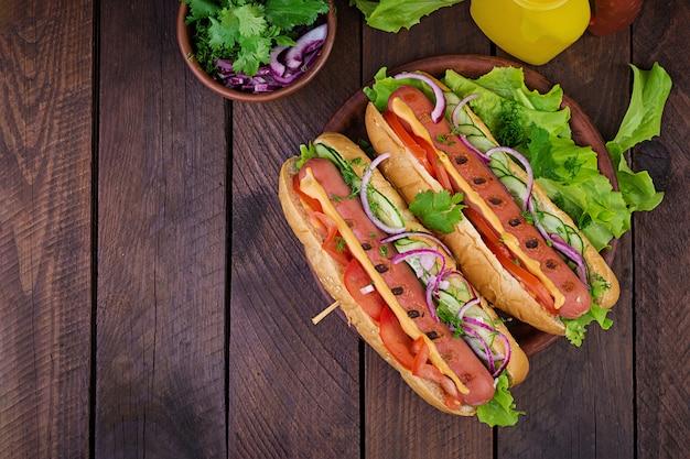 Cachorro-quente com lingüiça, pepino, tomate e alface na mesa de madeira escura. cachorro-quente de verão. vista do topo