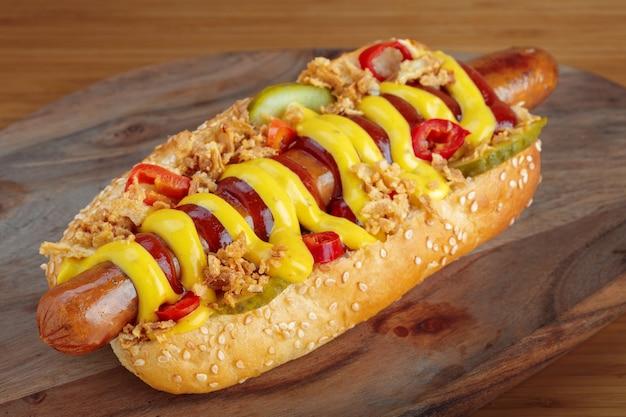 Cachorro-quente com mostarda amarela e ketchup na tábua de madeira