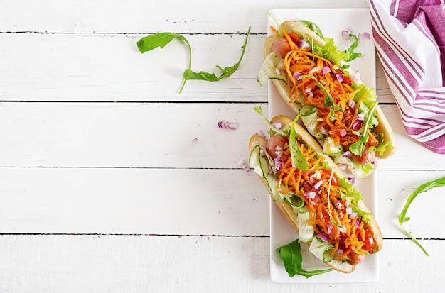 Cachorro-quente com pepino, cenoura, tomate e alface em fundo de madeira. menu de fast food. vista do topo