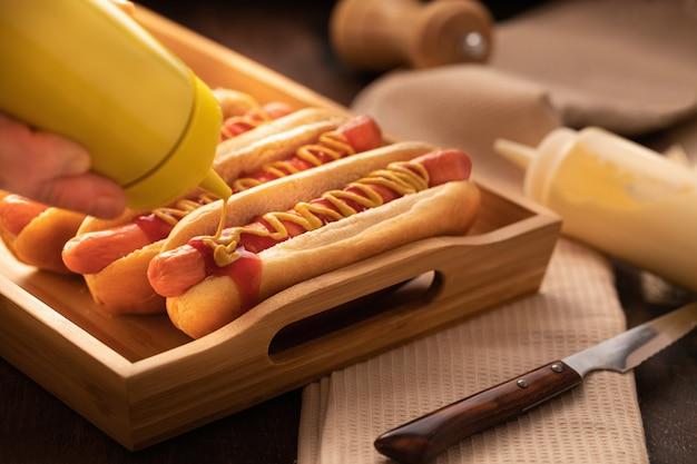 Cachorro-quente com pimenta, tomate, alface e salada misturam na madeira.