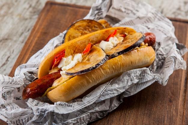 Cachorro-quente com salsicha, berinjela, queijo cottage, tomate e pimenta