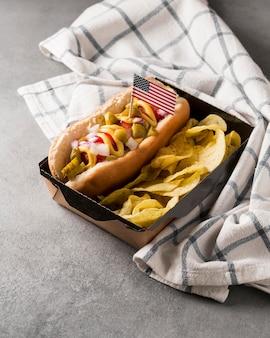 Cachorro-quente de ângulo alto e batatas fritas com bandeira americana