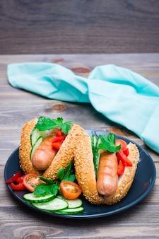 Cachorro-quente pronto-a-comer de salsichas fritas, pão de gergelim e legumes frescos em um prato sobre uma mesa de madeira