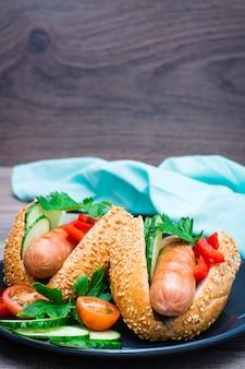 Cachorro-quente pronto para comer de salsichas fritas, pão de gergelim e legumes frescos em um prato sobre uma mesa de madeira