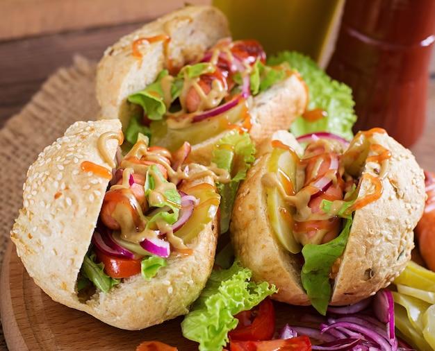Cachorro-quente - sanduíche com picles, cebola roxa e alface em fundo de madeira