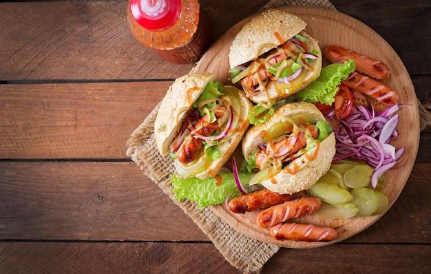Cachorro-quente - sanduíche com picles, cebola vermelha e alface em fundo de madeira. vista do topo