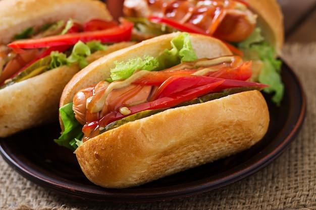 Cachorro-quente - sanduíche com picles, pimentão e alface em fundo de madeira