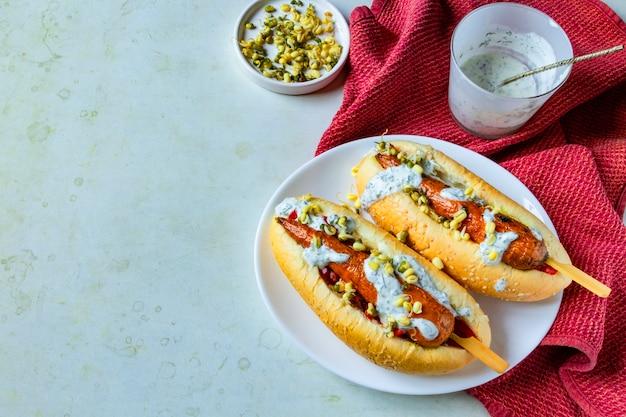 Cachorro-quente vegan de cenoura. placa branca com comida vegetariana de rua. conceito de refeição sem carne baseado em planta saudável.