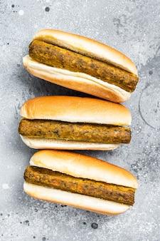 Cachorro-quente vegetariano com salsicha vegetariana sem carne. plano de fundo cinza. vista do topo.