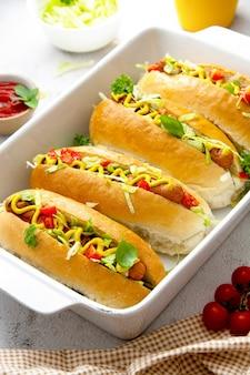 Cachorros-quentes caseiros com cobertura de mostarda e alface em um fundo brilhante. comida rápida.