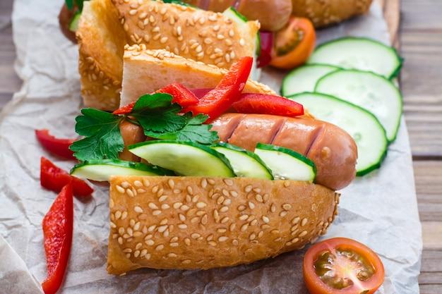 Cachorros-quentes com pão de gergelim e legumes frescos em um prato sobre uma mesa de madeira