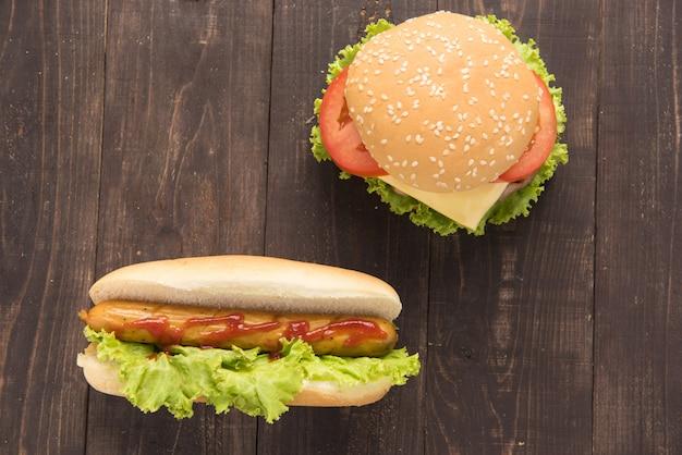 Cachorros-quentes e hambúrgueres na mesa de madeira