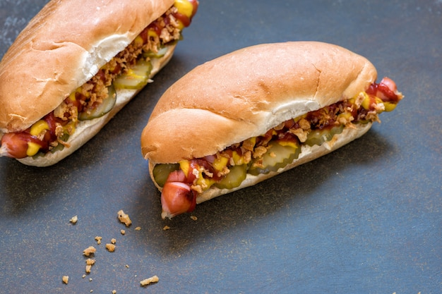 Cachorros-quentes grelhados com mostarda, ketchup e picles de endro