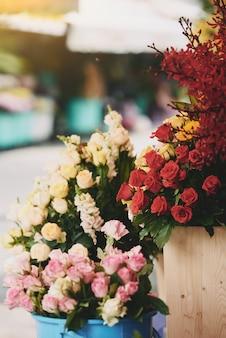 Cachos coloridos de rosas frescas, exibidos em baldes fora da loja de flores