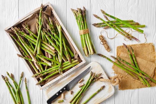 Cachos de aspargos verdes frescos em uma bandeja de madeira rústica e em uma tábua de cortar com uma faca na mesa de madeira branca