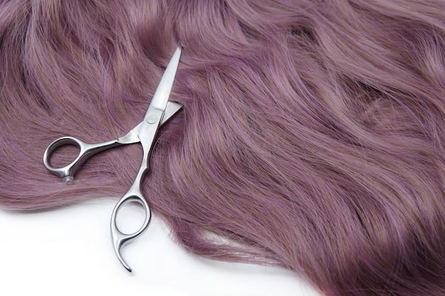 Cachos de cabelo e tesoura de cabeleireiro isolada no fundo branco