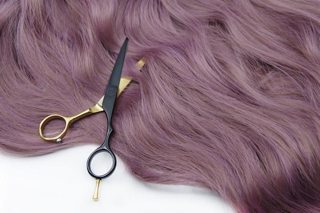Cachos de cabelo ruivo e tesoura de cabeleireiro isolada no fundo branco conceito de beleza