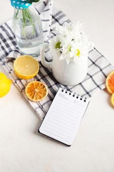 Cachos de flores frescas em vaso e jarra perto de frutas e o bloco de notas no guardanapo