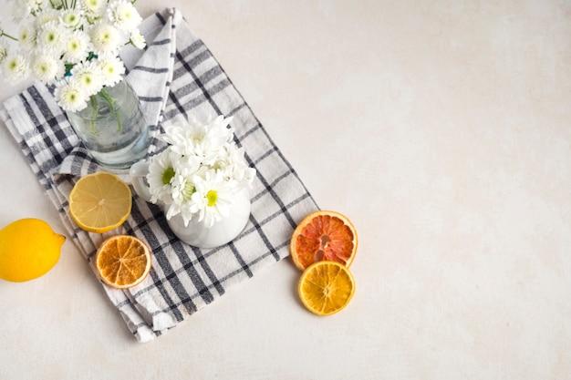 Cachos de flores frescas em vaso e jarro perto de frutas no guardanapo