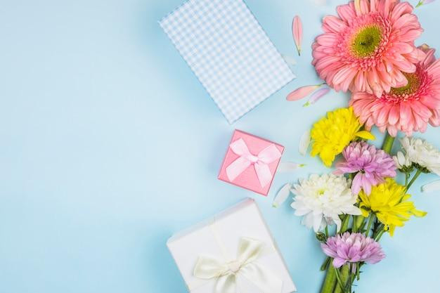 Cachos de flores frescas perto de caixas de presentes e decorações