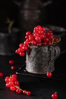 Cachos de groselhas vermelhas maduras em uma caneca de ferro em um fundo preto