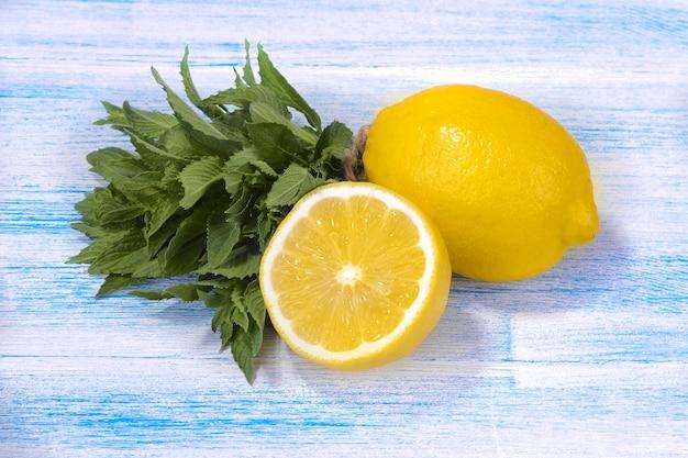 Cachos de hortelã fresca com limão em um fundo azul de madeira