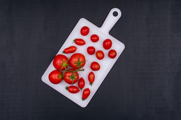 Cachos de tomate e tomate cereja vermelho na tábua branca sobre a superfície de pedra preta