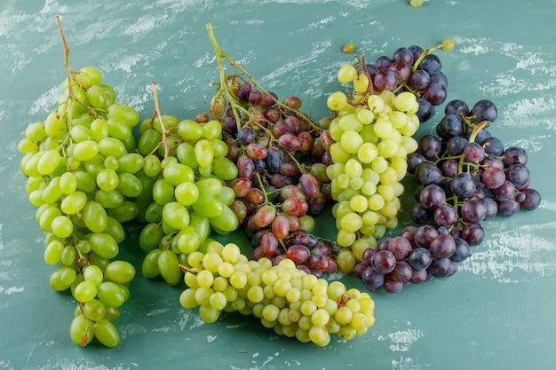 Cachos de uva em um fundo de gesso. colocação plana.