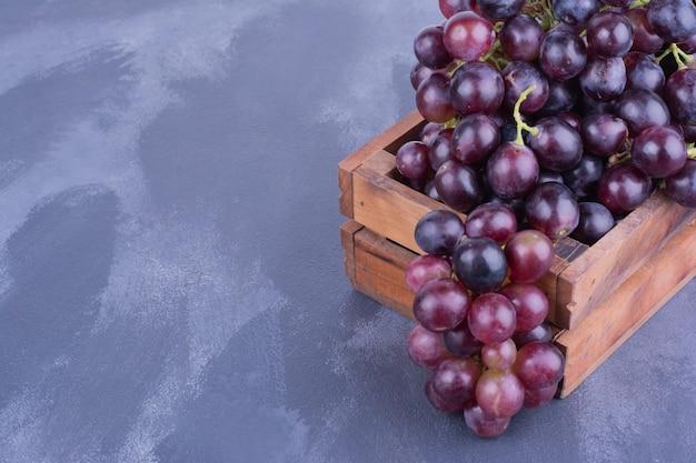 Cachos de uva em uma bandeja de madeira.