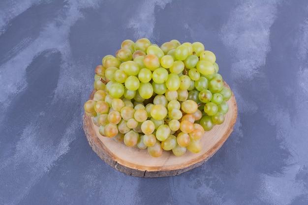 Cachos de uva em uma placa de madeira na superfície azul