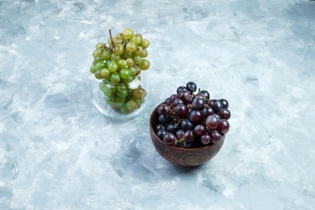Cachos de uva em uma tigela de barro e uma vista de alto ângulo do pote de vidro em um fundo cinza sujo